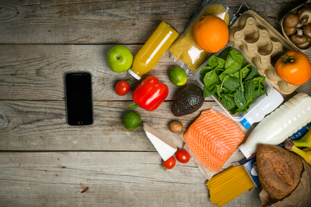 Online shopiing concept. Grocery shopping concept. Balanced diet concept. Fresh foods with shopping bag on rustic wood background, top view, copy space, flat lay