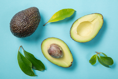 Slices of avocado on white background. Whole and half with leaves. Design element for product label, top view
