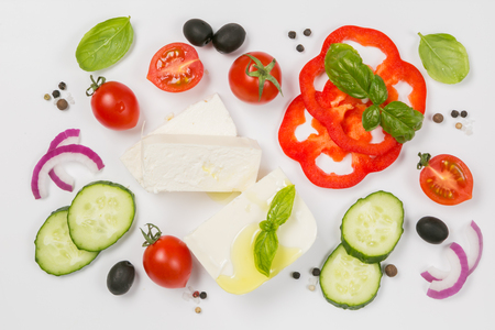 Healthy eating concept - selection of greek salad ingredients on white background, top view