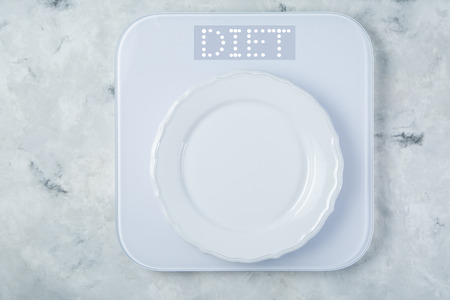 Weight loss concept - white plate on scales 스톡 콘텐츠