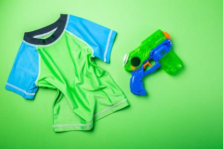 Summer fun concept - water gun and rash guard on bright background Stock Photo
