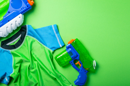 Summer fun concept - water gun and rash guard on bright background Stock Photo