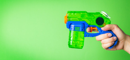 hand holding water gun in front of bright green background Stock Photo