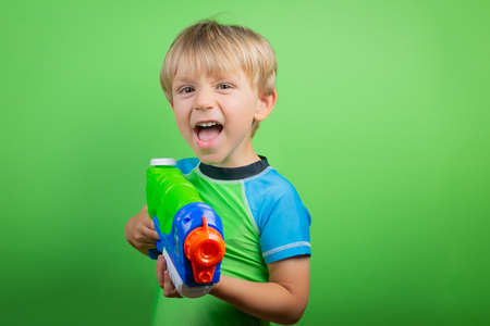 Boy holds water gun in front of bright green background Stock Photo