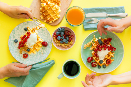 Family having breakfast with waffles, wipped cream, berries and granola, bright yellow background Stock Photo