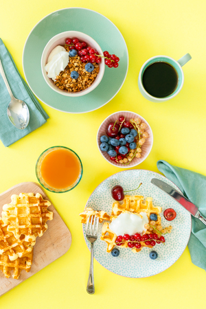 Breakfast with waffles, wipped cream, berries and granola