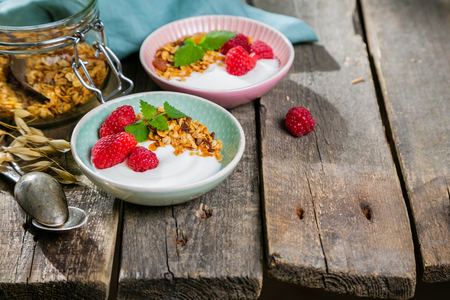 Summer breakfast - granola with strawberries and yogurt, rustic wood background, copy space