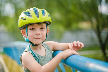 Boy wearing helmet, smiles in the park