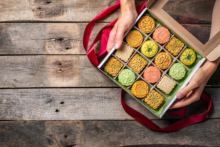 中秋祭りのコンセプト - プレゼントとしてユビングモンケーキを与える手、トップビュー 写真素材