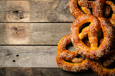 Oktoberfest concept - pretzels on rustic wood background, top view