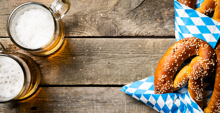 Oktoberfest concept - pretzels and beer on rustic wood background, top view Banco de Imagens