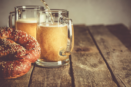 Oktoberfest concept - pretzels and beer on rustic wood background, copyspace for text Фото со стока