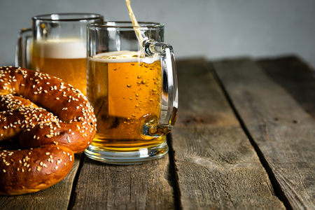 Oktoberfest concept - pretzels and beer on rustic wood background, copyspace for text Banco de Imagens