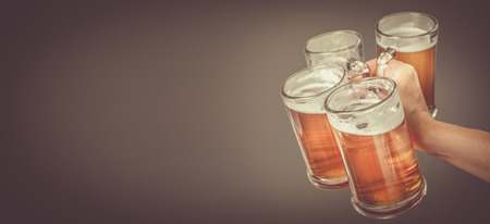 Oktoberfest concept - hand holding glasses with beer, grey background