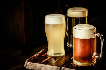 Selection of different types of beer in glasses in pub background