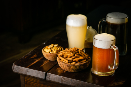 Selection of different types of beer and salty snacks s in pub