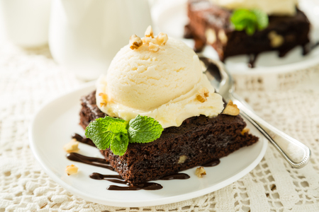 Chocolate brownie with vanilla ice cream, nuts and mint, served om white plate