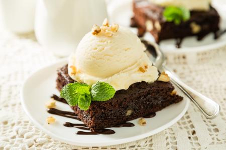 Schokoladen-Brownie mit Vanilleeis, Nüssen und Minze, serviert auf einem weißen Teller