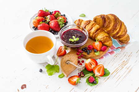 Breakfast - croissants with berries, jam white wood background