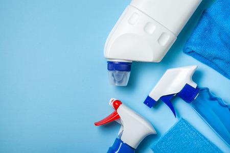 Suministros de limpieza: botellas, aerosoles esponja sobre fondo pastel brillante Foto de archivo