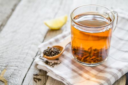Black tea in glass cup, closeup, rustic wood background