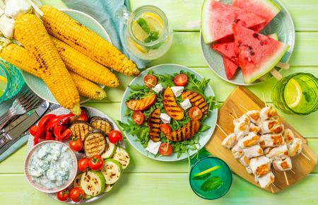 Summer bbq party concept - grilled chicken, vegetables, corn, salad, top view Stockfoto