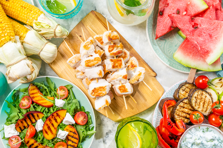 Summer bbq party concept - grilled chicken, vegetables, corn, salad, top view Stock Photo