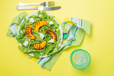Summer salad - arugula with grilled peaches, cheese