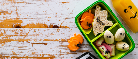Halloween style school lunch box - ghost sandwich, pumpkin carrots, bananas, juice