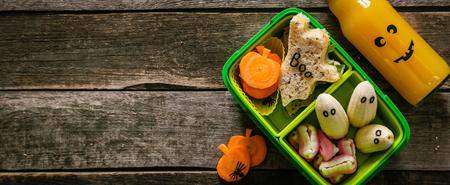 Halloween style school lunch box - ghost sandwich, pumpkin carrots, bananas, juice
