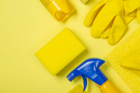 Cleaning supplies - yellow bottles, sprays sponge on bright pastel background