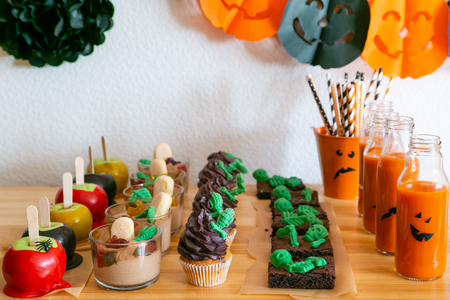 Halloween style party candy bar and decorations - brownies, cupcakes, mousse, caramel apples