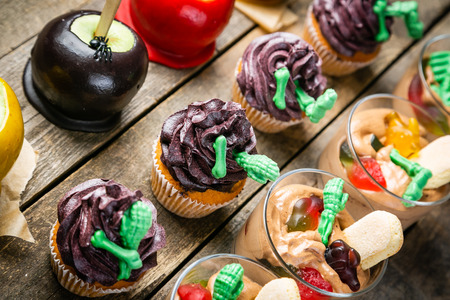 Selection of halloween party sweets - brownie, caramel apples, cupcakes, chocolate mousse, candies