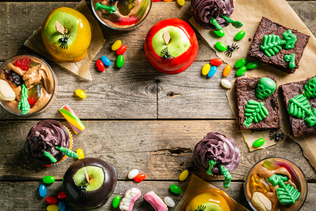 Selection of halloween party sweets - brownie, caramel apples, cupcakes, chocolate mousse, candies, top view