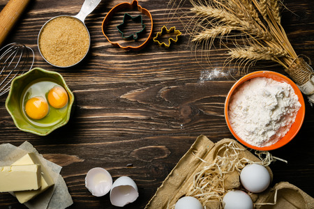 Baking concept - baking ingredients butter, flour, sugar, eggs on rustic wood background