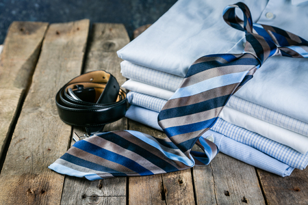 Selection of male clothes - stack of folded shirts, tie, belt, cufflinks Stock Photo