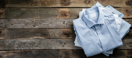 Stack of male folded shirts on rustic background