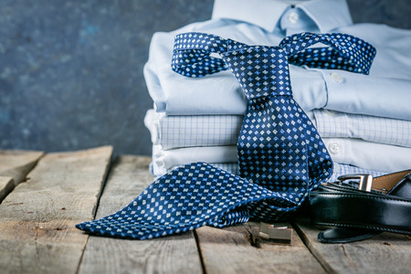 Selection of male clothes - stack of folded shirts, tie, belt, cufflinks