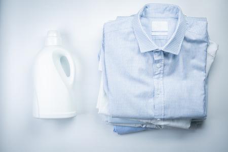 Concepto de lavado - montón de camisas dobladas con una botella de detergente