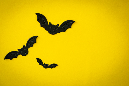 Halloween concept - spiders, bats, web paper crafts on bright background