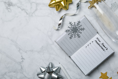 New year resolutions concept - notebook with list of goals and silver gold decorations