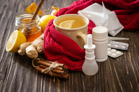 Medical care concept - ginger honey and lemon tea with drugs, pills and spray 版權商用圖片 - 110276903