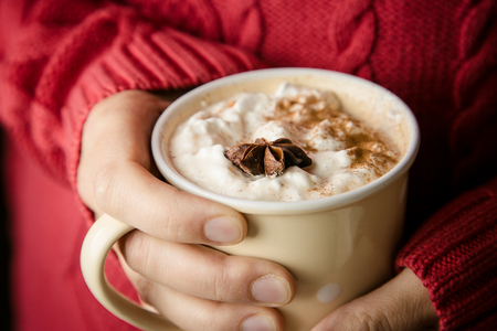 Hands holding cup of chai latte, toned Stock Photo