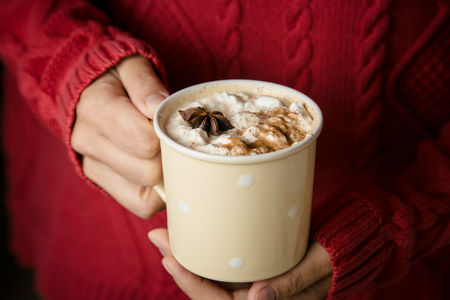 Hands holding cup of chai latte