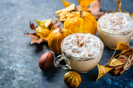 Pumpkin spice latte in glass cups on concrete blue background