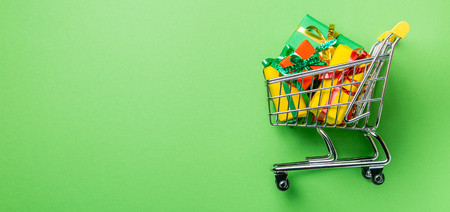 Online shopping concept - trolley cart full of presents Stock Photo
