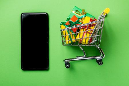 Online shopping concept - trolley cart full of presents Foto de archivo - 110866372