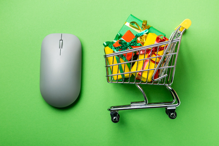 Online shopping concept - trolley cart full of presents Banco de Imagens