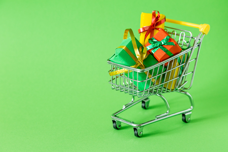 Online shopping concept - trolley cart full of presents Stockfoto