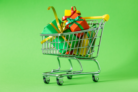 Online shopping concept - trolley cart full of presents 스톡 콘텐츠
